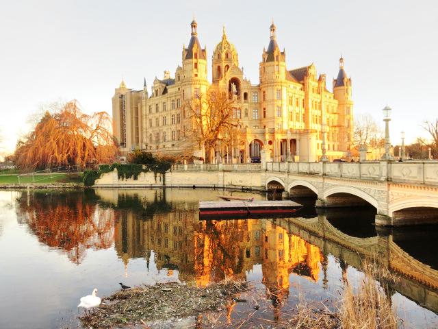 Schweriner Schloss bei Sonnenuntergang mit Schwan im Vordergrund
